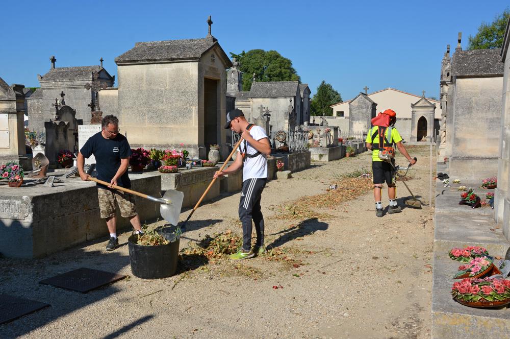Les services municipaux désherbant les allées du cimetière